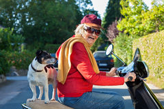 Elderly lady taking her dog for a scooter ride. Elderly lady in trendy modern clothes laughing happily as she takes her dog, a small jack russell terrier, for a royalty free stock photography