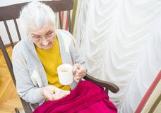 Elderly lady taking medication Royalty Free Stock Images