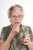 Elderly lady taking medicine Royalty Free Stock Photography