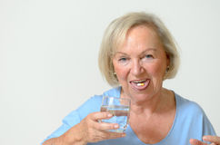 Elderly lady taking the prescribed dose of medicine. With a glass of water to treat a chronic disease caused by aging, portrait with copy space on gray Royalty Free Stock Photos