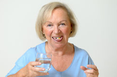 Elderly lady taking the prescribed dose of medicine. With a glass of water to treat a chronic disease caused by aging, portrait with copy space on gray Stock Images