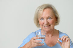 Elderly lady taking the prescribed dose of medicine. With a glass of water to treat a chronic disease caused by aging, portrait with copy space on gray Stock Photography