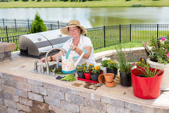 Elderly lady tending to her potted plants. Filling up a watering can at the sink in her outdoor patio kitchen as she prepares to water them, high angle view Stock Image