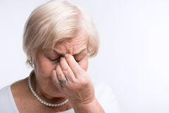 Elderly lady touching her head Royalty Free Stock Photography