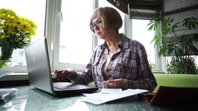 The elderly lady using internet banking in home. stock footage