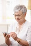 Elderly lady using smartphone. At home stock photos