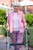 Elderly lady using a walker in the garden. Standing on a pathway with buildings in the background smiling at the camera stock photography