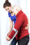 Elderly lady walking on crutches. With young woman stock photography