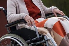Elderly lady on wheelchair outdoors Stock Photos