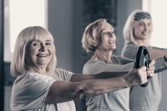 Elderly lady working out with weight disc with friends. Gaining strength. Joyful elderly women exercising with a weight disc together with her peer friends while Royalty Free Stock Photos