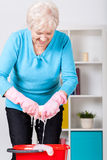 Elderly lady wringing cloth Stock Image