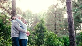Elderly lifestyle people with couple of caucasian active senior kissing in relationship with green plants nature in background. Retired in outdoor leisure stock footage
