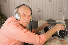 Elderly Listening Radio While Looking at Camera Royalty Free Stock Photo