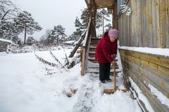 Elderly lone woman cleans the snow near home. Royalty Free Stock Image