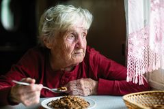 Elderly lone woman eats sitting at the table stock images
