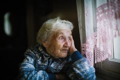 Elderly Lone Woman In The House Sitting At The Table Looking Out The Window Stock Photos