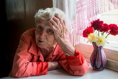 Elderly lone woman looks sadly sitting near the window. Stock Image