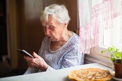 Elderly Lone Woman Sits With A Smartphone In Her Hands. Stock Photo