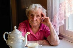 Elderly lone woman sitting at the table. royalty free stock images