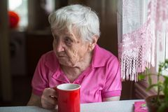 Elderly lone woman with tea mug in the kitchen. stock photos