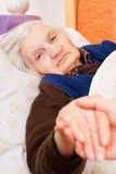 Elderly lonely woman rests in the bed Stock Photos