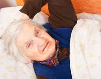 Elderly lonely woman rests in the bed Royalty Free Stock Photos