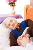 Elderly lonely woman rests in the bed Stock Images