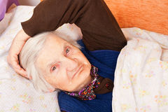 Elderly lonely woman rests in the bed. Elderly lonely woman in the bed Royalty Free Stock Image