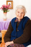 Elderly lonely woman sits on the bed Royalty Free Stock Photos
