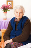 Elderly lonely woman sits on the bed Royalty Free Stock Image