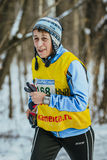 Elderly looking woman athlete running on snowy road in forest Royalty Free Stock Photo