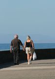 Elderly Lovers. Elderly man and middle aged woman holding hands and walking along a beach promenade Royalty Free Stock Image