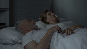 Elderly male in bed looking at female sleeping near, turning back to her, fight. Stock footage stock video footage