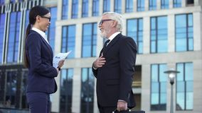 Elderly male in business suit meeting young female partner near office center royalty free stock photos