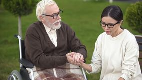 Elderly male comforting lady upset with bad diagnosis, visit to nursing home. Stock photo stock photography