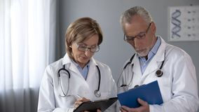 Elderly male and female doctors consulting on treatment, comparing results royalty free stock images