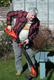 Elderly male gardener trimming grass edges. An elderly gardener trimming the grass edges in a garden with strimmer stock photography
