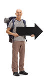 Elderly male hiker holding an arrow pointing right Stock Photo