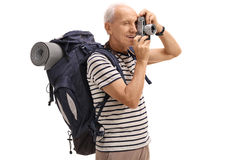 Elderly male hiker taking a picture with a camera. Isolated on white background Royalty Free Stock Photos
