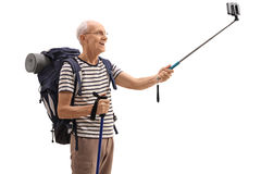 Elderly male hiker taking a selfie with a stick. Isolated on white background Stock Images