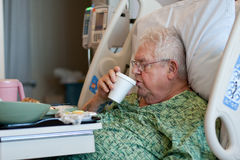 Elderly male hospital patient drinks water Royalty Free Stock Photography