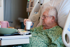 Elderly male hospital patient drinks water Royalty Free Stock Photo