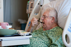 Elderly male hospital patient eats lunch. A white-haired elderly man sits up in a hospital bed and eats lunch.  He wears a green hospital gown, wears glasses Stock Images