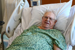 Elderly male hospital patient is happy. A white-haired elderly man sits up in a hospital bed and looks happy.  He wears a green hospital gown, wears glasses, and Royalty Free Stock Photos