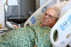 Elderly male hospital patient holds TV remote Royalty Free Stock Images