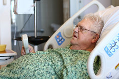 Elderly male hospital patient holds TV remote Stock Photos