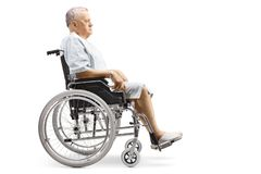 Elderly male patient in a hospital gown sitting in a wheelchair stock photo