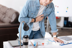 Elderly male person feeling discomfort in left side. Symptoms of heart attack. Inert man standing behind his workplace putting left hand on the table while Stock Image
