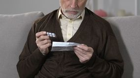 Elderly male reading pills dosage, side effect and precautions, pharmacology. Stock footage stock video
