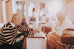 Elderly Male Rehabilitation. Patients Play Chess. Elderly Male Rehabilitation. Senior Man and Woman Play Chess. Nursing Home. Doctor and Nurse Stand Nearby royalty free stock photography